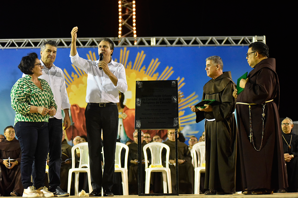 Foto de Davi Pinheiro traz o Governador do Ceará, Camilo Santana sobre o palco, com a mão direita levantada. O governador anuncia os investimentos para cidade de Canindé. Ao lado de Camilo Santana, frades de Canindé.