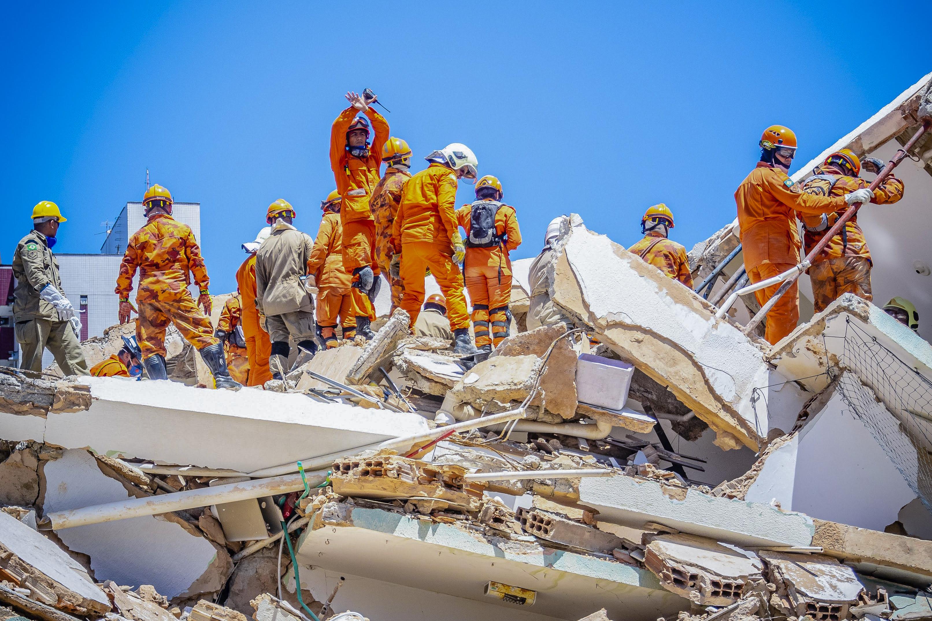 Forças de segurança trabalham para resgatar pessoas com vida em local de desabamento